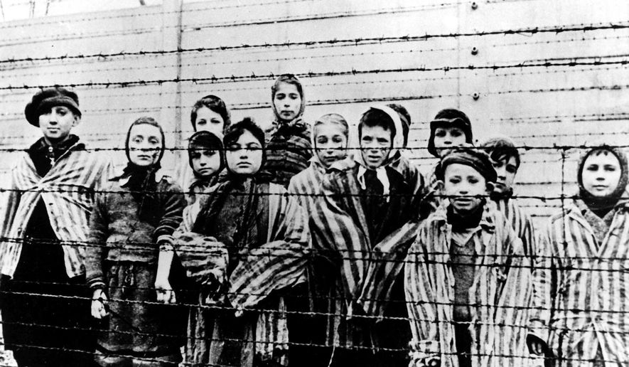 A picture taken just after the liberation by the Soviet army in January 1945, shows a group of children wearing concentration camp uniforms at the time behind barbed wire fencing in the Oswiecim (Auschwitz) Nazi concentration camp. Germany has agreed to provide more than a half-billion euros to aid Holocaust survivors struggling under the burdens of the coronavirus pandemic, the organization that negotiates compensation with the German government said Wednesday. (AP Photo/CAF pap, file)