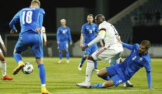 Iceland's Holmar Eyjolfsson, right, and Belgium's Romelu Lukaku, centre, battle for the ball during the UEFA Nations League soccer match between Iceland and Belgium at the Laugardalsvollur stadium in Reykjavik, Iceland, Wednesday, Oct. 14, 2020. (AP Photo/Brynjar Gunnarsson)