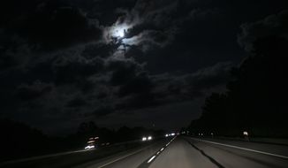 """The moon shines through clouds along a highway in New Columbia, Ill., near Vienna, Ill., on Saturday, Aug. 1, 2020. """"Sundown towns"""" like Vienna were places where Black people were allowed in during the day to work or shop but had to be gone by nightfall. Today, some still exist in various forms, enforced now by tradition and fear rather than by rules. (AP Photo/Wong Maye-E)"""