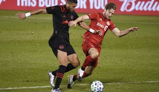 New York Red Bulls' Amro Tarek, left, and Toronto FC's Patrick Mullins fight for control of the ball during the first half of an MLS soccer match, Wednesday, Oct. 14, 2020, in East Hartford, Conn. (AP Photo/Jessica Hill)
