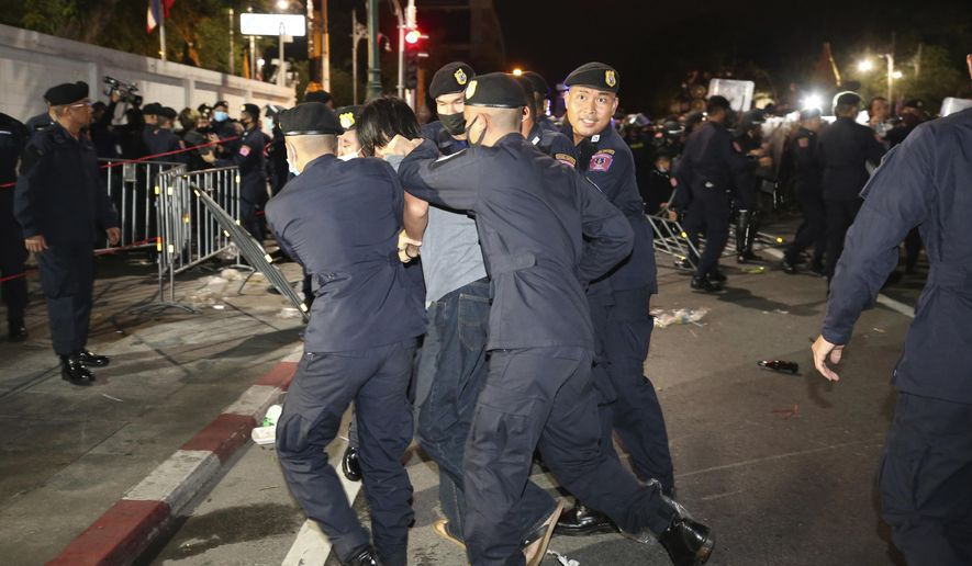 Thai policemen take away a pro-democracy protester during a demonstration in Bangkok, Thailand, Thursday, Oct. 15, 2020. Thai police dispersed a group of protesters holding an overnight rally outside the prime minister's office. (AP Photo/Rapeephat Sitichailapa)