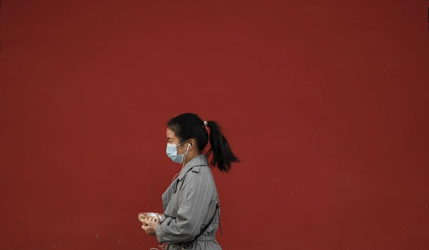 A woman wearing a face mask to help curb the spread of the coronavirus holds her breakfast meal while walking by a red wall in Beijing, Wednesday, Oct. 14, 2020. (AP Photo/Andy Wong)