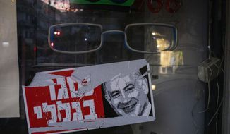 """A poster reads """"closed because of me """" with an image of Israel's Prime Minister Benjamin Netanyahu on a closed shop in Tel Aviv, Israel, Tuesday, Oct. 13, 2020. Israel has had one of the largest income gaps and poverty rates among developed economies, even before the coronavirus pandemic. The country has a few high earners concentrated in the lucrative high-tech sector, while many Israelis barely get by as civil servants, in service industries or as small business owners. (AP Photo/Ariel Schalit)"""