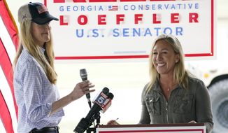 Marjorie Taylor Greene, right, introduces Sen. Kelly Loeffler, R-Ga., left, during a news conference on Thursday, Oct. 15, 2020, in Dallas, Ga. (AP Photo/Brynn Anderson)