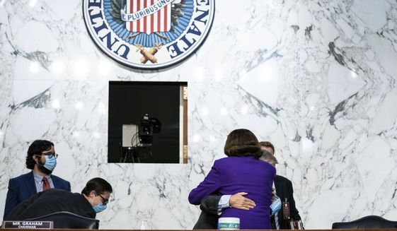 Sen. Lindsey Graham, R-S.C., hugs Sen. Dianne Feinstein, D-Calif., following the fourth day of a confirmation hearing for Supreme Court nominee Amy Coney Barrett, before the Senate Judiciary Committee, Thursday, Oct. 15, 2020, on Capitol Hill in Washington. (Anna Moneymaker/The New York Times via AP, Pool)