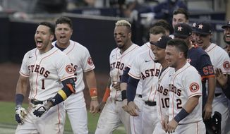 Players celebrate Houston Astros Carlos Correa's (1) walk off home run during the ninth inning in Game 5 of a baseball American League Championship Series, Tuesday, Dec. 15, 2020, in San Diego. The Astros defeated the Rays 4-3 and the Rays lead the series 3-2 games. (AP Photo/Gregory Bull)