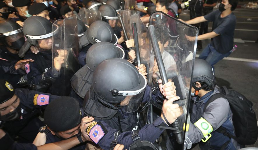 Pro-democracy protesters push Thai policemen with riot shields during a demonstration in Bangkok, Thailand, Thursday, Oct. 15, 2020. Thai police dispersed a group of protesters holding an overnight rally outside the prime minister's office. (AP Photo/Rapeephat Sitichailapa)