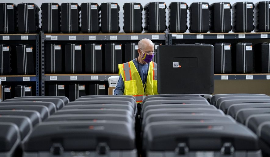 FILE - In this Sept. 3, 2020, file photo, a worker prepares tabulators for the upcoming election at the Wake County Board of Elections in Raleigh, N.C. Early in-person voting starts Thursday, Oct. 15, 2020, in all 100 counties in North Carolina, where the historically popular form of casting ballots has been upstaged this fall by people voting by mail during the COVID-19 pandemic. (AP Photo/Gerry Broome, file)