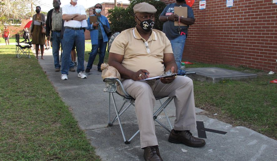 Richard Williams sits in a folding chair, filling out paperwork, as he waits in line to vote early in Savannah, Ga., on Wednesday, Oct. 14, 2020. Black people are going to the polls by the thousands and waiting in lines for hours to vote early in Georgia. (AP Photo/Russ Bynum)