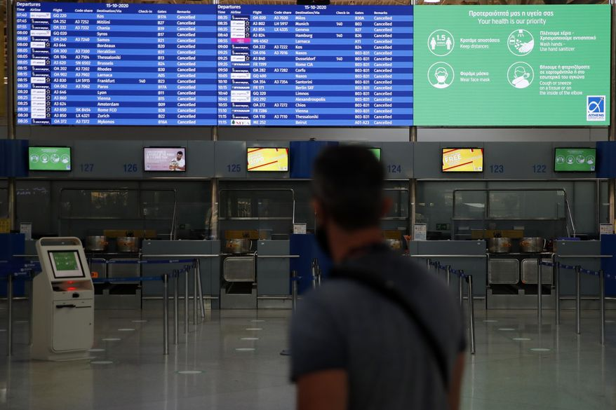 A board shows the cancelled flights as a man walks at the empty Eleftherios Venizelos International Airport during a 24-hour strike in public sector in Athens, Thursday, Oct. 15. 2020. Greece's air traffic electronic engineers and air traffic control personnel, participate in the 24-hour strike organised by civil servant union ADEDY demanding, among other things, better pay for health and education workers and the need for more recruitments of medical workers amidst the pandemic. (AP Photo/Thanassis Stavrakis)