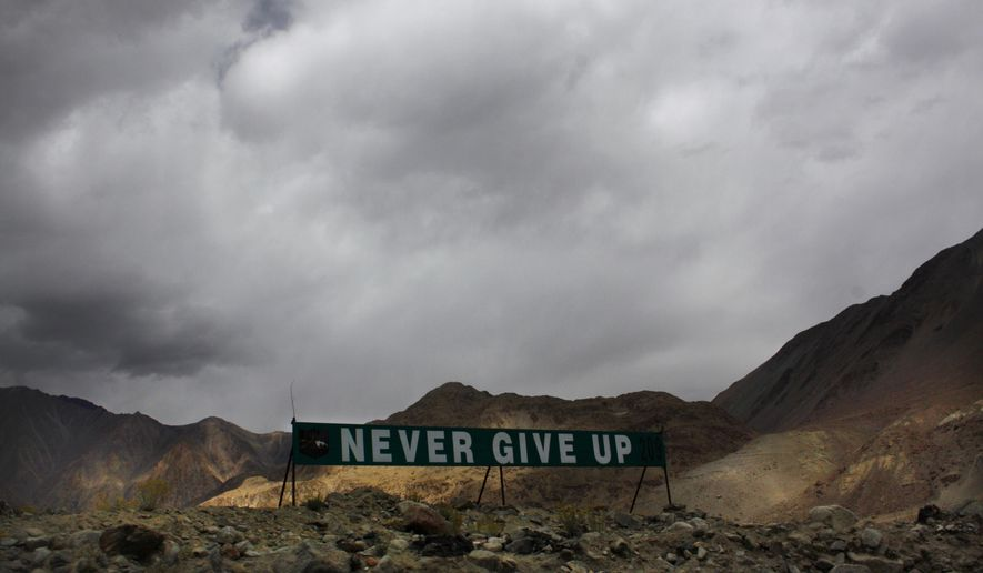 In this Sept. 14, 2017, file photo, a banner erected by the Indian army stands near Pangong Tso lake near the India-China border in India's Ladakh area. Senior Indian and Chinese military commanders are holding fresh talks aimed at ending a monthslong standoff along their disputed border. Monday's talks were being held on the Indian side of the frontier. No details were immediately made available. (AP Photo/Manish Swarup, File)