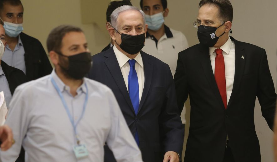 Israeli Prime Minister Benjamin Netanyahu, center, arrives at the Israeli Knesset, or Parliament in Jerusalem ahead of the discussion of the peace treaty with the United Arab Emirates, Thursday, Oct. 15, 2020. (Alex Kolomoisky/Pool Photo via AP)