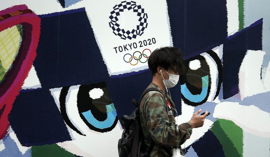 A man walks in front of an advertisement for the Tokyo 2020 Olympics Thursday, Oct. 8, 2020, in Tokyo. Typhoon Chan-hom is approaching Japan's main island with authorities warning of strong winds and torrential rains. (AP Photo/Eugene Hoshiko)  **FILE**