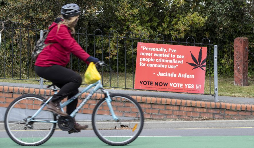 A cyclist rides past a sign in support of making marijuana legal in Christchurch, New Zealand, Thursday, Oct. 15, 2020. New Zealanders are poised to decide on two crucial social issues during an election on Saturday, Oct. 17, whether to legalize recreational marijuana and whether to legalize euthanasia. (AP Photo/Mark Baker)