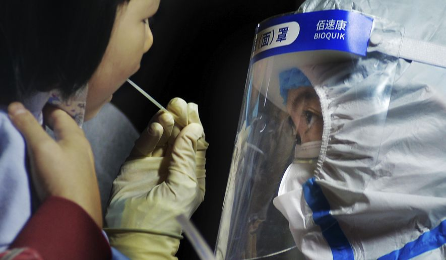 A medical staff takes a swab from a child near a residential area in Qingdao in east China's Shandong province on Tuesday, Oct. 13, 2020. A hospital president and the director of the health commission in the northern Chinese city of Qingdao have been fired after China's latest coronavirus outbreak, authorities said Thursday, Oct. 15, 2020. (Chinatopix via AP)
