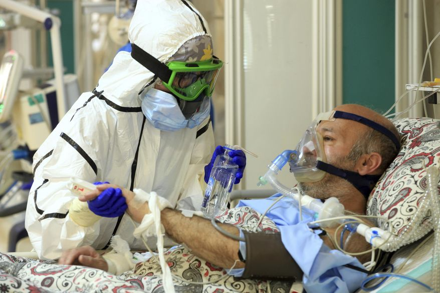 In this Wednesday, Oct. 14, 2020, photo provided by the Iranian Health Ministry, a medic tends to a COVID-19 patient at the Shohadaye Tajrish Hospital in Tehran, Iran. Iran is confronting a new surge of infections that is filling hospitals and cemeteries alike. (Akbar Badrkhani/Iranian Health Ministry via AP)