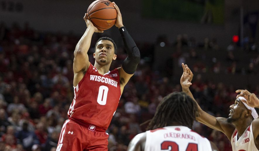 FILE - In this Feb. 15, 2020, file photo, Wisconsin guard D'Mitrik Trice (0) puts up a jump shot against Nebraska guard Dachon Burke Jr. (11) and Nebraska forward Yvan Ouedraogo (24) during the second half of an NCAA college basketball game in Lincoln, Neb. Wisconsin is trying not to think about its missed opportunity from last March as the Badgers seek to build on the momentum they established before the pandemic shut down the 2019-20 season prematurely. (AP Photo/John Peterson, File)