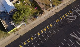 In this photo taken by a drone, the phrase 'Black Lives Matter' is written in yellow paint on a parking lot East of Noto Arts and Entertainment District in Topeka in support of the national movement.Officials plan to wash away the words Black Lives Matter from the Topeka parking lot because the yellow block letters were painted without permission in a decision that has angered activists. Shawnee County County commissioner Bill Riphahn says the Parks and Recreation department is removing it next week, but organizers can ask to get a new, county-approved mural. (Evert Nelson/The Topeka Capital-Journal via AP)