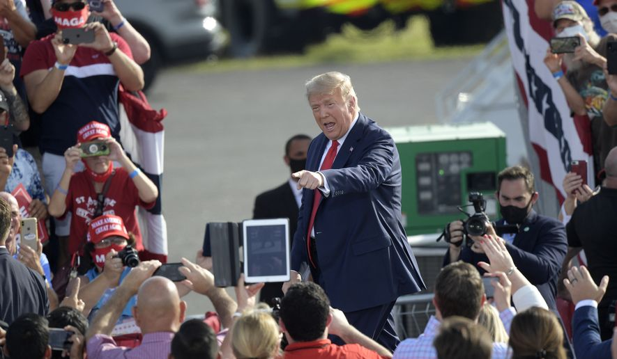 President Donald Trump points to supporters after arriving for a campaign rally at the Ocala International Airport, Friday, Oct. 16, 2020, in Ocala, Fla. (AP Photo/Phelan M. Ebenhack)