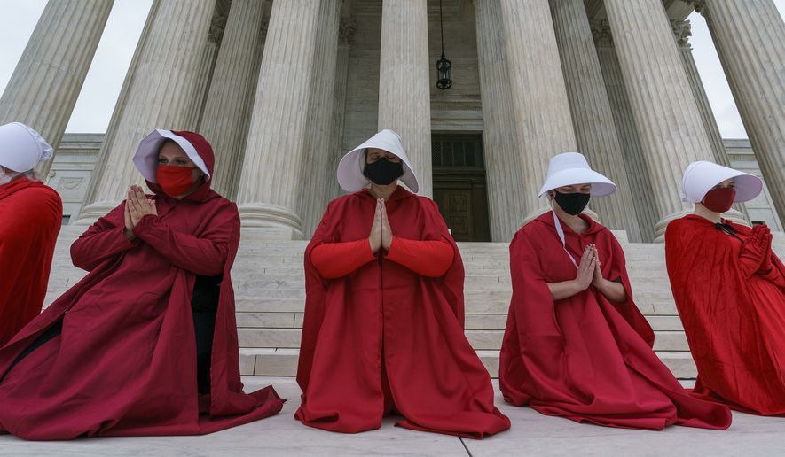 """Activists opposed to the confirmation of President Donald Trump's Supreme Court nominee, Judge Amy Coney Barrett, are dressed as characters from """"The Handmaid's Tale,"""" at the Supreme Court on Capitol Hill in Washington, Sunday, Oct. 11, 2020. Barrett's confirmation hearing began Monday before the Republican-led Senate Judiciary Committee. (AP Photo/J. Scott Applewhite)"""
