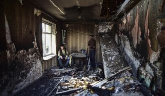 Men look at the damage in a house a day after four Azerbaijani Turks were killed and several others were wounded in a shelling in a cemetery by Armenian forces, in the city of Tartar, Azerbaijan, Friday, Oct. 16, 2020. The conflict between Armenia and Azerbaijan continues for a third week despite a Russia-brokered cease-fire deal, as both sides exchanged accusations and claims of new attacks over the separatist territory of Nagorno-Karabakh. (Ismail Coskun/IHA via AP)