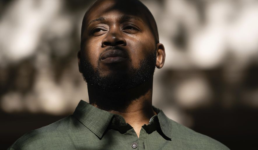 """Theo Brown poses for a portrait outside his home in Marietta, Ga., on Wednesday, Oct. 14, 2020. While at the Drug Enforcement Administration's Training Academy, Brown said he was once pepper-sprayed three times in a single training exercise while other trainees were sprayed once. It got to the point, he said, that other trainees didn't want to work near him because of the """"special attention"""" he was receiving. (AP Photo/Elijah Nouvelage)"""
