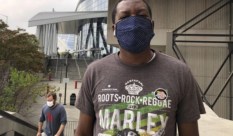 In this Oct. 15, 2020, photo Tunde Ezekiel poses for a photo after voting early at State Farm Arena in downtown Atlanta. A Democrat, Ezekiel said he came out to vote early to avoid Election Day lines and to ensure that his vote against President Donald Trump is counted. (AP Photo/Kate Brumback)