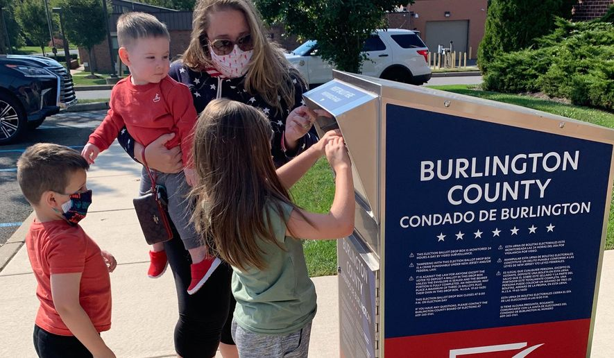 Nicole Flaherty, top, stands with her kids as her 7-year old daughter Madelyn places the ballot in the box in the Burlington County ballot box in Cinnaminson, N.J. on Wednesday, Oct. 7, 2020. While holding 1-year-old Colin, she opens the dropbox door as 5-year-old James, left, watches Madelyn push the ballots through the slot. (AP Photo/Christina Paciolla)