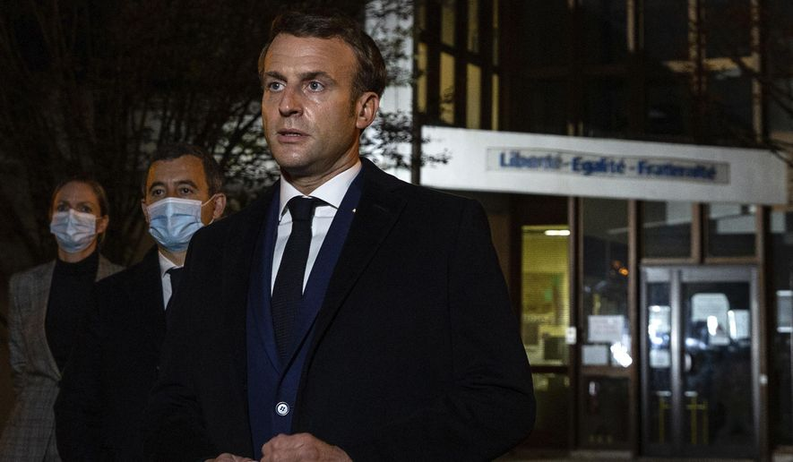 "French President Emmanuel Macron, flanked by French Interior Minister Gerald Darmanin, second left, speaks in front of a high school Friday Oct.16, 2020 in Conflans Sainte-Honorine, northwest of Paris, after a history teacher who opened a discussion with high school students on caricatures of Islam's Prophet Muhammad was beheaded. French President Emmanuel Macron denounced what he called an ""Islamist terrorist attack"" against a history teacher decapitated in a Paris suburb Friday, urging the nation to stand united against extremism. (Abdulmonam Eassa, Pool via AP)"