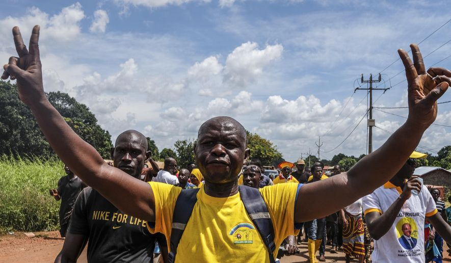 A supporter of the ruling Rally of the Guinean People (RPG) party joins others to demonstrate against the opposition Union of Democratic Forces of Guinea (UFDG) party and to block the visit of their leader, in the streets of Kankan, Guinea Sunday, Oct. 11, 2020. The stage is set for Oct. 18 presidential elections pitting incumbent President Alpha Conde, 82, who is bidding for a third term, against opposition leader Cellou Dalein Diallo, who was previously defeated by Conde in both the 2010 and 2015 elections. (AP Photo/Sadak Souici)