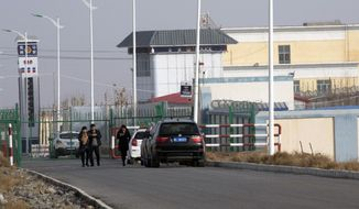 FILE - In this Dec. 3, 2018, file photo, people walk by a police station by the front gate of the Artux City Vocational Skills Education Training Service Center in Artux in western China's Xinjiang region. A coalition of human-rights groups has met with the International Olympic Committee over calls to pull the 2022 Winter Olympics out of Beijing. (AP Photo/Ng Han Guan, File)
