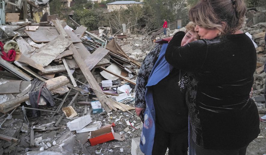A neighbour comforts home owner, Lida Sarksyan, left, near her house destroyed by shelling from Azerbaijan's artillery during a military conflict in Stepanakert, the separatist region of Nagorno-Karabakh, Saturday, Oct. 17, 2020. The latest outburst of fighting between Azerbaijani and Armenian forces began Sept. 27 and marked the biggest escalation of the decades-old conflict over Nagorno-Karabakh. The region lies in Azerbaijan but has been under control of ethnic Armenian forces backed by Armenia since the end of a separatist war in 1994. (AP Photo)