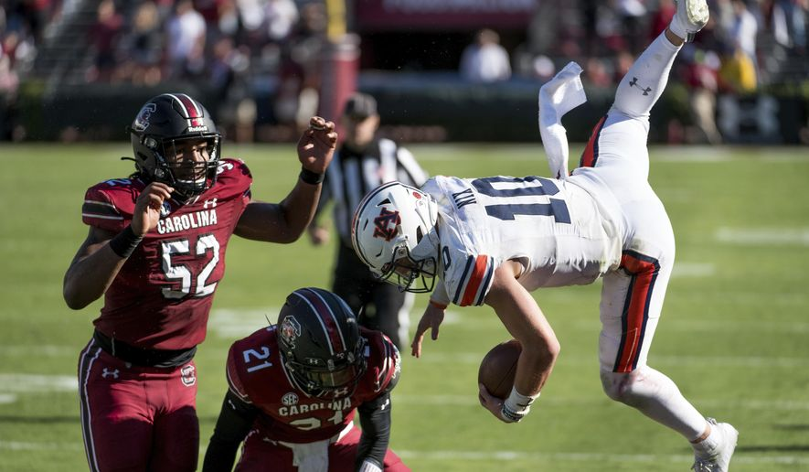 Auburn quarterback Bo Nix (10) is knocked out of bounds by South Carolina defensive back Shilo Sanders (21) and Kingsley Enagbare (52) during the second half of an NCAA college football game Saturday, Oct. 17, 2020, in Columbia, S.C. South Carolina defeated Auburn 30-22. (AP Photo/Sean Rayford)