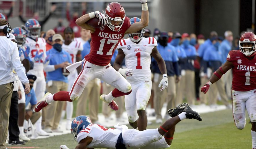 Arkansas defensive back Hudson Clark (17) leaps over Mississippi running back Tylan Knight (4) as he returns an interception during the second half of an NCAA college football game Saturday, Oct. 17, 2020, in Fayetteville, Ark. (AP Photo/Michael Woods)