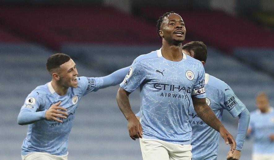 Manchester City's Raheem Sterling, front, celebrates after scoring his side's opening goal during the English Premier League soccer match between Manchester City and Arsenal at the Etihad stadium in Manchester, England, Saturday, Oct. 17, 2020. (Martin Rickett/Pool via AP)