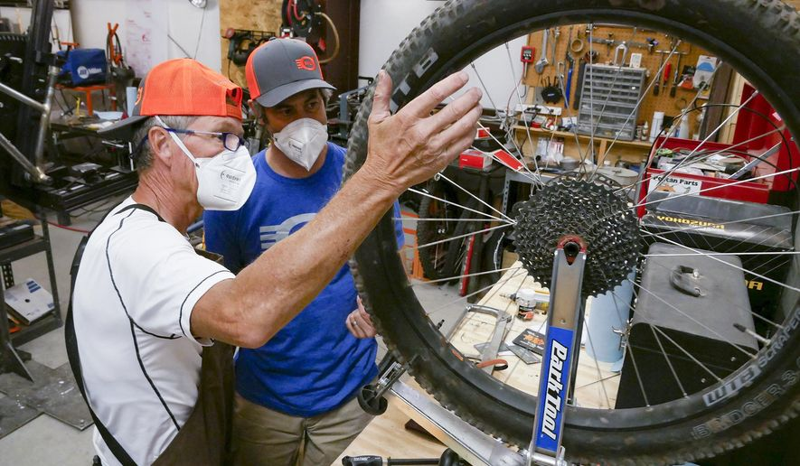 This Sept. 29, 2020, image shows volunteer Jan Bear, left, and shop owner Charlie O'Leary inspecting a mountain bike wheel at O'Leary Built Bicycles in Santa Fe, New Mexico. With limited access to gyms, people are snatching up bikes as soon as they hit the sales floor. In Santa Fe, retailers are struggling to keep bikes in stock. (Matt Dahlseid/Santa Fe New Mexican, via AP)