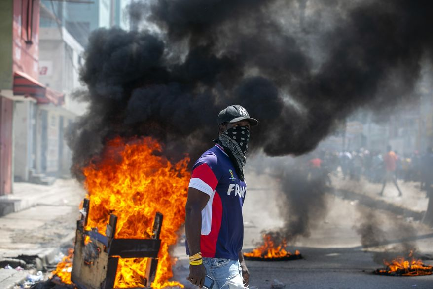 A protester walks past burning barricades during a protest demanding the resignation of President Jovenel Moise in Port-au-Prince, Haiti, Saturday, Oct. 17, 2020. The country is currently experiencing a political impasse without a parliament and is now run entirely by decree under Moise. ( AP Photo/Dieu Nalio Chery)