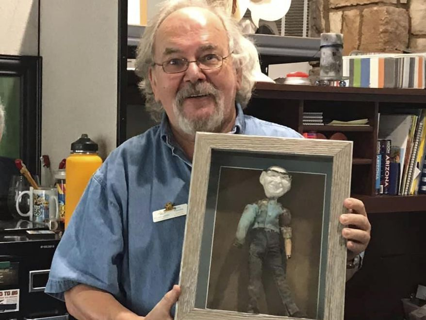 Jan Cassies, director of the Lake Havasu Visitor Center, poses with a doll on Wednesday, Oct. 7, 2020, that was buried for nearly 50 years inside the city's landmark London Bridge, in Lake Havasu City, Ariz. Tourism officials are still unsure what to do with the doll, which was found in 2018. (Brandon Messick/Today's News-Herald via AP)