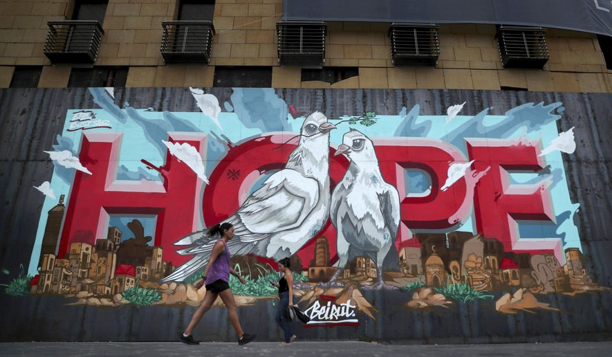 "Women walk past a graffiti ""Hope"" painted on metals barrier that closed the entrance of a hotel that was damaged by Aug. 4 explosion that hit the seaport of Beirut, Lebanon, Monday, Oct. 12, 2020. A year ago, hundreds of thousands of Lebanese took to the streets in protests nationwide that raised hopes among many for a change in a political elite that over that decades has run the country into the ground.  (AP Photo/Bilal Hussein)"
