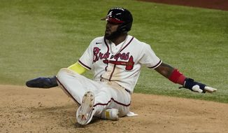 Atlanta Braves' Marcell Ozuna watches after getting called out at home after leaving third early during the third inning in Game 5 of a baseball National League Championship Series against the Los Angeles Dodgers Friday, Oct. 16, 2020, in Arlington, Texas. (AP Photo/Tony Gutierrez)