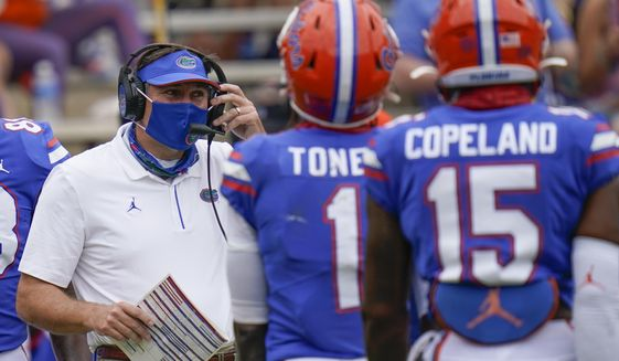 Florida head coach Dan Mullen, left, talks with wide receivers Kadarius Toney (1) and Jacob Copeland (15) during a timeout in the first half of an NCAA college football game against South Carolina, Saturday, Oct. 3, 2020, in Gainesville, Fla. (AP Photo/John Raoux, Pool)