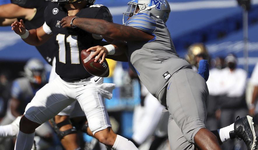 Memphis defensive lineman O'Bryan Goodson (1) drags down Central Florida quarterback Dillon Gabriel (11) during an NCAA college football game Saturday, Oct. 17, 2020, in Memphis, Tenn. (Patrick Lantrip/Daily Memphian via AP)