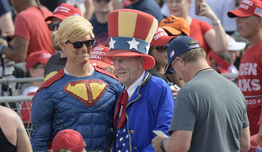 Supporters of President Donald Trump pose for photos while walking through the crowd during a campaign rally at the Ocala International Airport, Friday, Oct. 16, 2020, in Ocala, Fla. (AP Photo/Phelan M. Ebenhack)