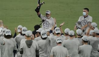 Tampa Bay Rays manager Kevin Cash holds the American League championship trophy following their victory against the Houston Astros in Game 7 of a baseball American League Championship Series, Saturday, Oct. 17, 2020, in San Diego. The Rays defeated the Astros 4-2 to win the series 4-3 games. (AP Photo/Ashley Landis)