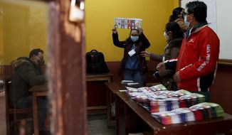 Electoral officials count ballots after polls closed for presidential elections in La Paz, Bolivia, Sunday, Oct. 18, 2020. (AP Photo/Juan Karita)