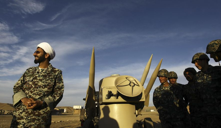 FILE - In this Nov. 13, 2012 file photo, an Iranian clergyman stands next to missiles and army troops, during a manoeuvre, in an undisclosed location in Iran. A decade-long U.N. arms embargo on Iran that bared it from purchasing foreign weapons like tanks and fighter jets expired Sunday, Oct. 18, 20202, as planned under its nuclear deal with world powers, despite objections from the United States. (Majid Asgaripour/Mehr News Agency via AP, File)