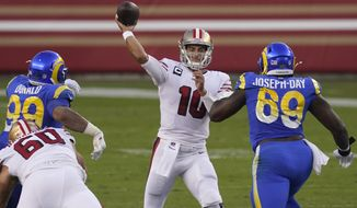 San Francisco 49ers quarterback Jimmy Garoppolo (10) passes between Los Angeles Rams defensive end Aaron Donald (99) and nose tackle Sebastian Joseph-Day (69) during the first half of an NFL football game in Santa Clara, Calif., Sunday, Oct. 18, 2020. (AP Photo/Tony Avelar)