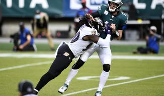 Philadelphia Eagles' Carson Wentz (11) is hit by Baltimore Ravens' Pernell McPhee (90) during the second half of an NFL football game, Sunday, Oct. 18, 2020, in Philadelphia. (AP Photo/Derik Hamilton)