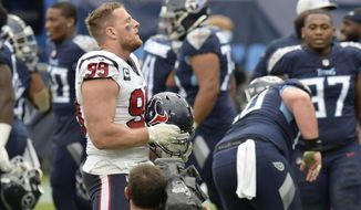 Houston Texans defensive end J.J. Watt (99) stands on the field as Tennessee Titans players celebrate after overtime of an NFL football game Sunday, Oct. 18, 2020, in Nashville, Tenn. The Titans won 42-36. (AP Photo/Mark Zaleski)