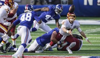 Washington Football Team quarterback Kyle Allen (8) loses control of the ball during the second half of an NFL football game against the New York Giants, Sunday, Oct. 18, 2020, in East Rutherford, N.J. Giants linebacker Tae Crowder (48) recovered the ball and scored a touchdown on the play. (AP Photo/John Minchillo)